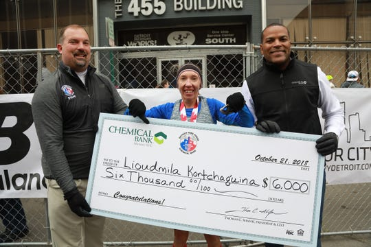 LioudmilaKortchaguina, 47, of Markham, Ontario accepts a check from Tim Gruber, of Detroit Free Press and Michigan.com, and Donnell White, of Chemical Bank, after finishing first, during the 41st Annual Detroit Free Press/Chemical Bank Marathon in Detroit on Sunday, Oct. 21, 2018.