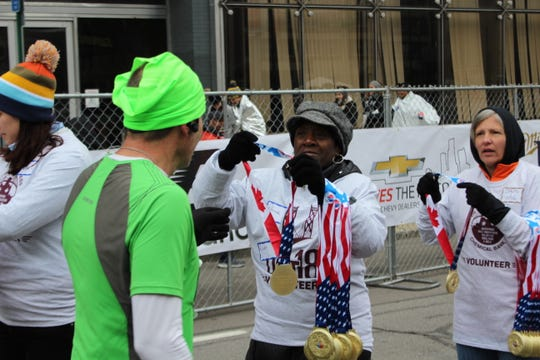 Southfield resident Rhonda Jackson, center,  presents a medal to marathoner Steve Guilliat of St. Clair.
