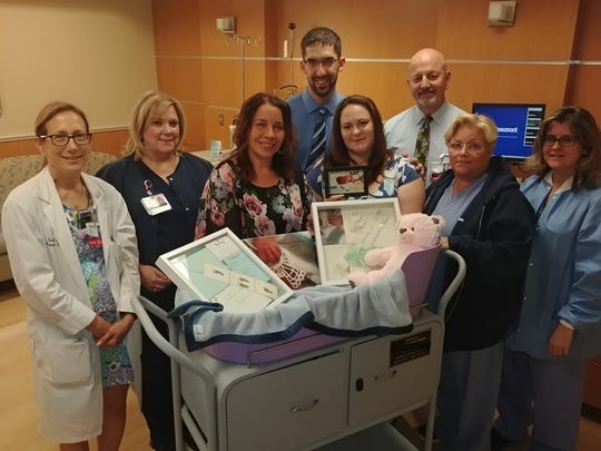 "Left to Right: Dr. Sara Garmel, Darlene Baczynski, Angie Winton, Scott Duley and Alison Duley, and Dearborn Hospital Staff in July of 2018 after the Duley's son William died after his birth. Metro Detroit Share donated their first temperature-controlled ""Caring Cradle"" to the couple to give them more time to say goodbye."