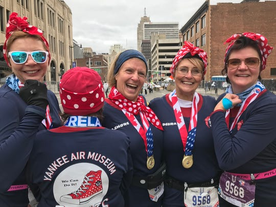 From left, Wendy Albers, Caro Miranda (back turned), Lenore Bolthouse, Debra Carver and Brenda Presnell reunite after the marathon relay, attired as Rosie the Riveter.