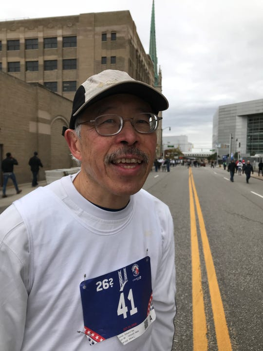 """Ed Yee, 66, of Plymouth pauses on his way to the """"bag pick-up"""" after running his 41st Detroit marathon -- keeping alive his streak going back to the event's founding in 1978."""