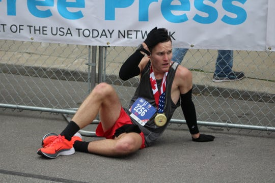 Nashville resident Nick French takes a moment to recover after finishing runner-up at the Detroit Free Press/Chemical Bank Marathon on Sunday, Oct. 21, 2018 in downtown Detroit.