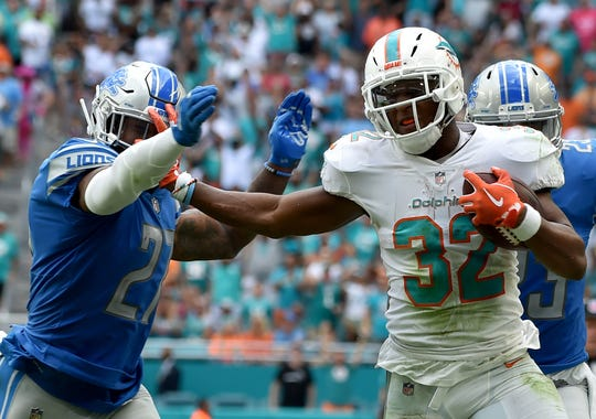 Dolphins running back Kenyan Drake stiff arm Lions free safety Glover Quin en route to a touchdown during the second half of the Lions' 32-21 win on Sunday, Oct. 21, 2018, in Miami Gardens, Fla.
