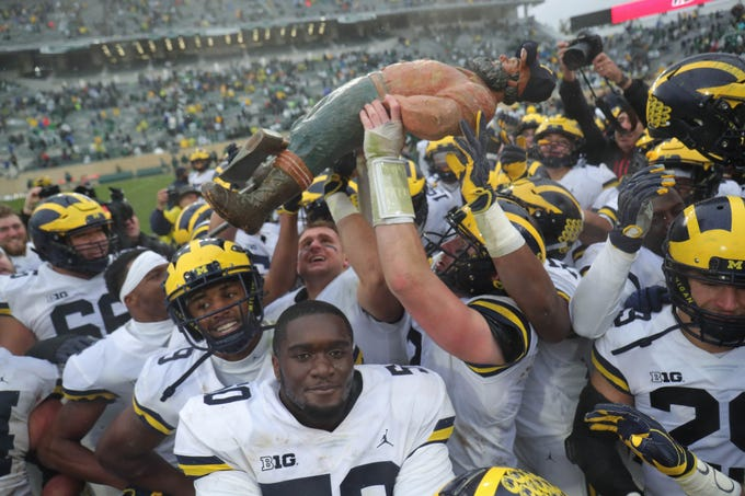 Michigan players raise the Paul Bunyan Trophy after the 21-7 win over Michigan State, Saturday, Oct. 20, 2018 at Spartan Stadium in East Lansing.