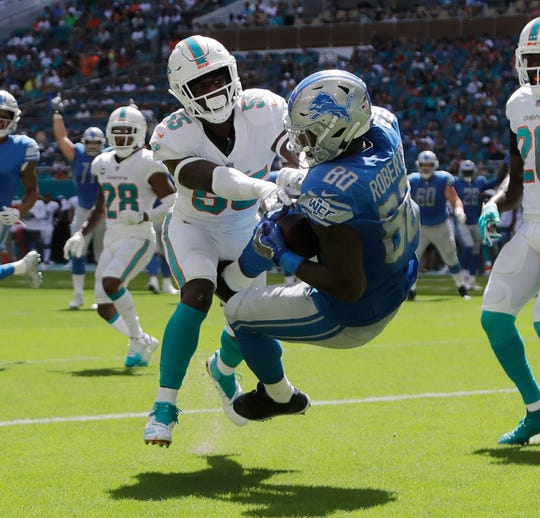 Lions tight end Michael Roberts catches a pass in the endzone for a touchdown as Dolphins linebacker Jerome Baker defends, during the first half on Sunday, Oct. 21, 2018, in Miami Gardens, Fla.