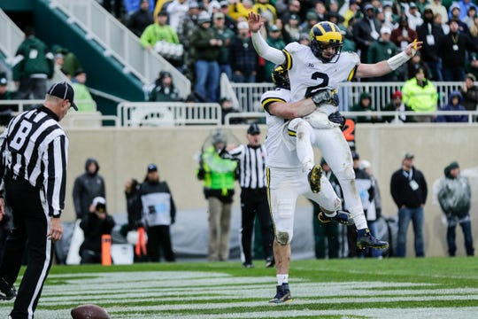 Michigan quarterback Shea Patterson (2) and fullback Ben Mason celebrate a touchdown against Michigan State during the second half at Spartan Stadium in East Lansing, Saturday, Oct. 20, 2018.