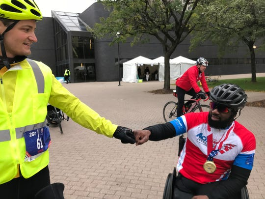 From left, bicycle guide John Pogoncheff of Lansing fist-bumps handcyclist Anthony Robinson of Akron, Ohio, after Robinson's 11th-place finish in Sunday's Detroit marathon.