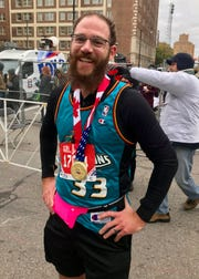 Joe Fratangelo, 34, of Berkley, sports a teal-era Detroit Pistons jersey of Grant Hill while running his first half-marathon at the Detroit Free Press/Chemical Bank Marathon.