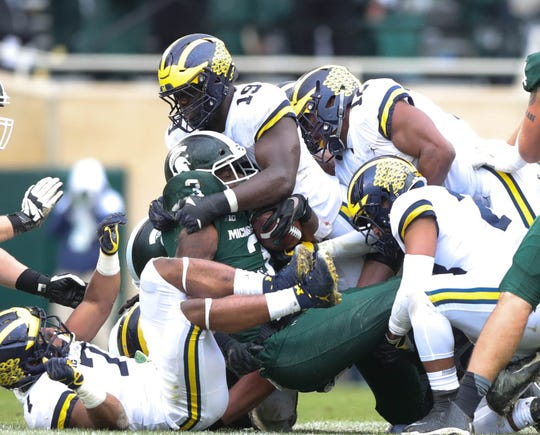 Michigan's Kwity Paye (19) tackles Michigan State's LJ Scott during the second half Saturday, Oct. 20, 2018 at Spartan Stadium in East Lansing.