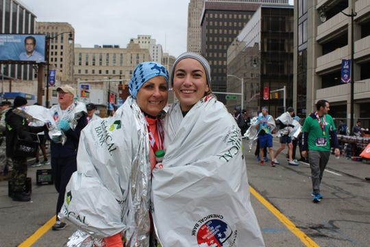Aliceann Rotondo and Alexis Soave celebrate after finishing the Detroit Free Press/Chemical Bank Marathon's 13.1-mile international race. Soave did a cartwheel as she crossed the finish line on Sunday, Oct. 21, 2018.