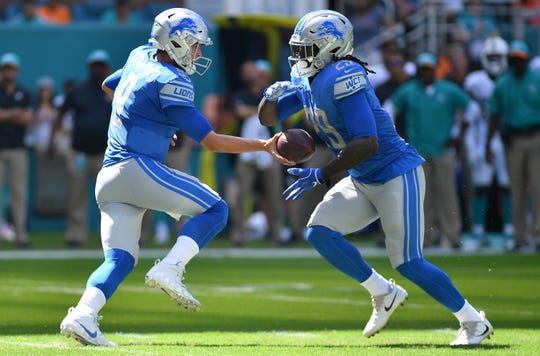 Lions quarterback Matthew Stafford hands the ball off to LeGarrette Blount in the first quarter of the Lions' 32-21 win on Sunday, Oct. 21, 2018, in Miami Gardens, Fla.