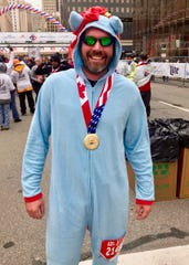 Dan Dobrovich, 36, of Livonia, promised his 7-year-old daughter that he'd wear a blue unicorn onsie while running in the Detroit Free Press/Chemical Bank Marathon on Sunday, Oct. 21, 2018.