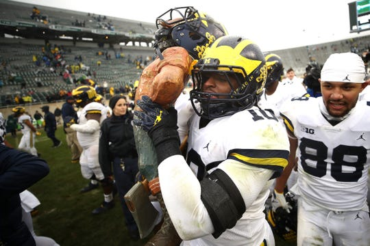 Michigan's Devin Bush carries the Paul Bunyan Trophy, after defeating Michigan State, 21-7, Saturday, Oct. 20, 2018, in East Lansing.