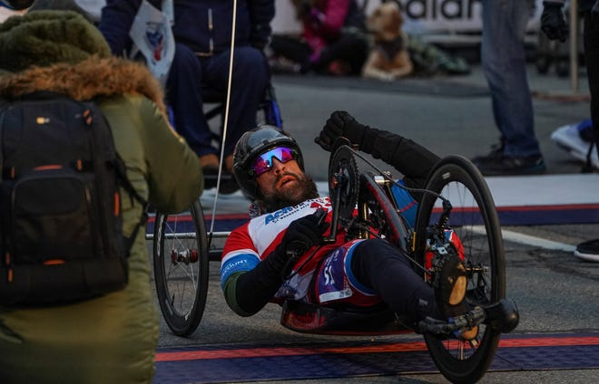 Hand cyclist Tom Davis crosses the finish line in first place during the 41st Annual Detroit Free Press/Chemical Bank Marathon in Detroit on Sunday, Oct. 21, 2018.