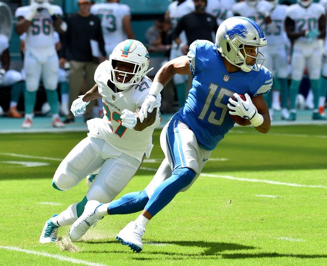 Lions wide receiver Golden Tate carries the ball against Dolphins running back Kalen Ballage on a punt return during the first half on Sunday, Oct. 21, 2018, in Miami Gardens, Fla.