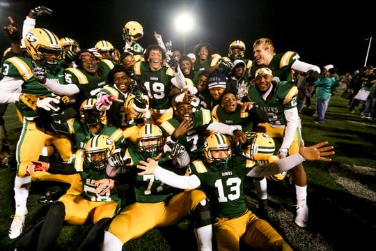 Farmington Hills Harrison players celebrate their win over rival Farmington on Friday night.