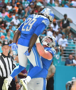 Lions running back LeGarrette Blount is hoisted into the air by lineman Frank Ragnow after Blount's touchdown run in the second quarter of Sunday's victory.