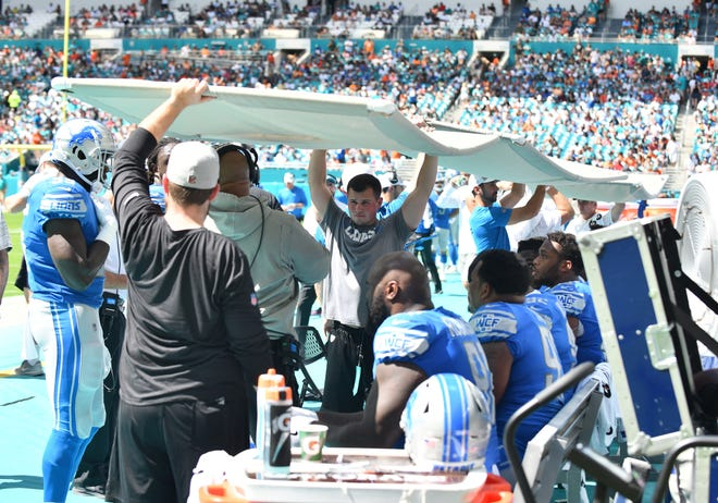 Lions personnel hold screens up over the players to help with the heat and sun as temperatures reached into the high 80s and low 90s during the game at Hard Rock Stadium.