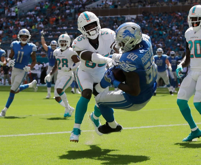 Detroit Lions tight end Michael Roberts catches a pass in the end zone for a touchdown as Miami Dolphins linebacker Jerome Baker defends during the first quarter.