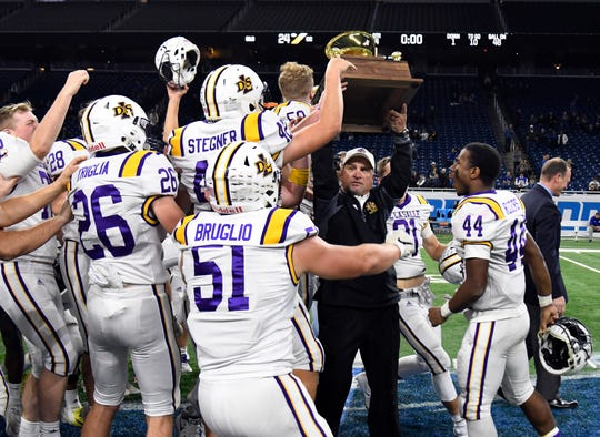 Warren De La Salle football head coach Mike Giannone is swarmed by his team as he hoists the championship trophy for defeating Detroit Catholic Central int he Catholic League Prep Bowl AB Division Championship.