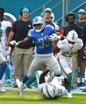 Lions running back Kerryon Johnson runs for a long first down past a pair of Dolphins defenders in the first quarter of Sunday's win in Miami.