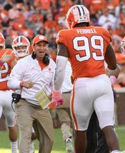 Clemson Head Coach Dabo Swinney smiles as Clemson defensive lineman Clelin Ferrell (99) come back in after stopping NC State during the fourth quarter in Memorial Stadium on Saturday, October 20, 2018.