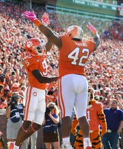 Clemson wide receiver Tee Higgins (5) celebrates with defensive lineman Christian Wilkins (42) after scoring against NC State during the 1st quarter Saturday, October 20, 2018 at Clemson's Memorial Stadium.