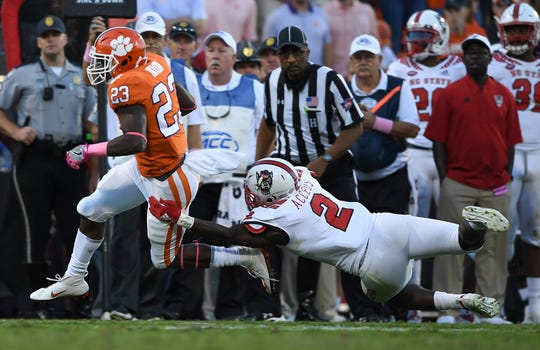 NC State linebacker Louis Acceus (2) tries to stop Clemson running back Lyn-J Dixon (23) during the 4th quarter Saturday, October 20, 2018 at Clemson's Memorial Stadium.