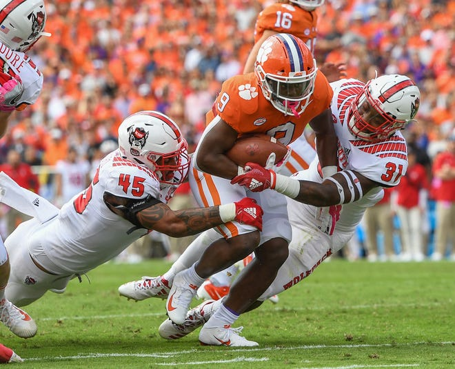 NC State defensive end Darian Roseboro (45), left, and safety Jarius Morehead (31) try to stop Clemson running back Travis Etienne (9) during the 1st quarter Saturday, October 20, 2018 at Clemson's Memorial Stadium.