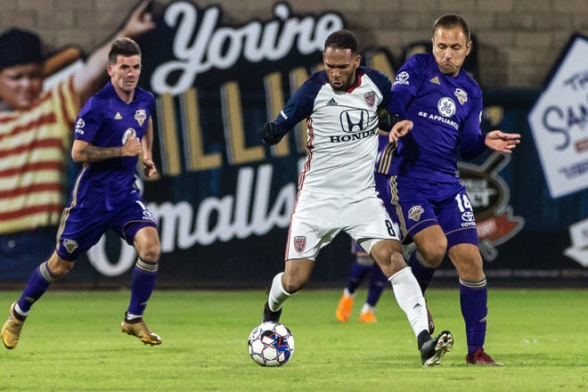 Indy Eleven's Matt Watson tries to hold off Louisville City FC defenders in Saturday's USL playoff match.