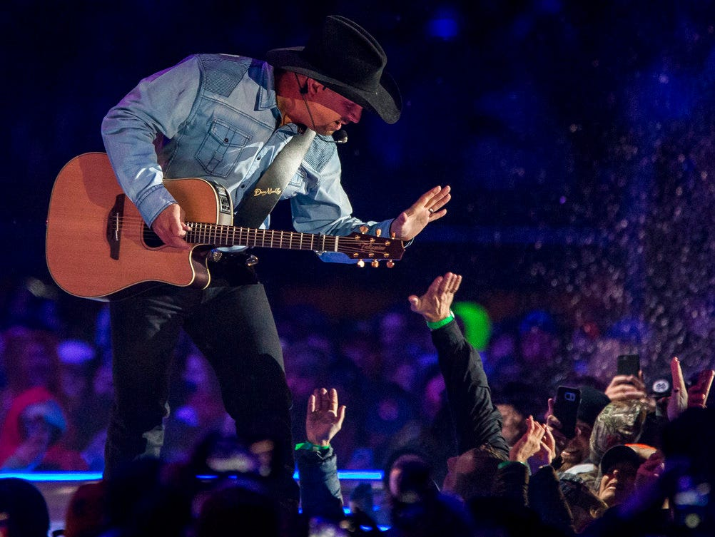 Garth Brooks high-fives a fan as he performs before a sold-out crowd at Notre Dame Stadium Saturday, Oct. 20, 2018, in South Bend, Ind. (Robert Franklin/South Bend Tribune via AP)