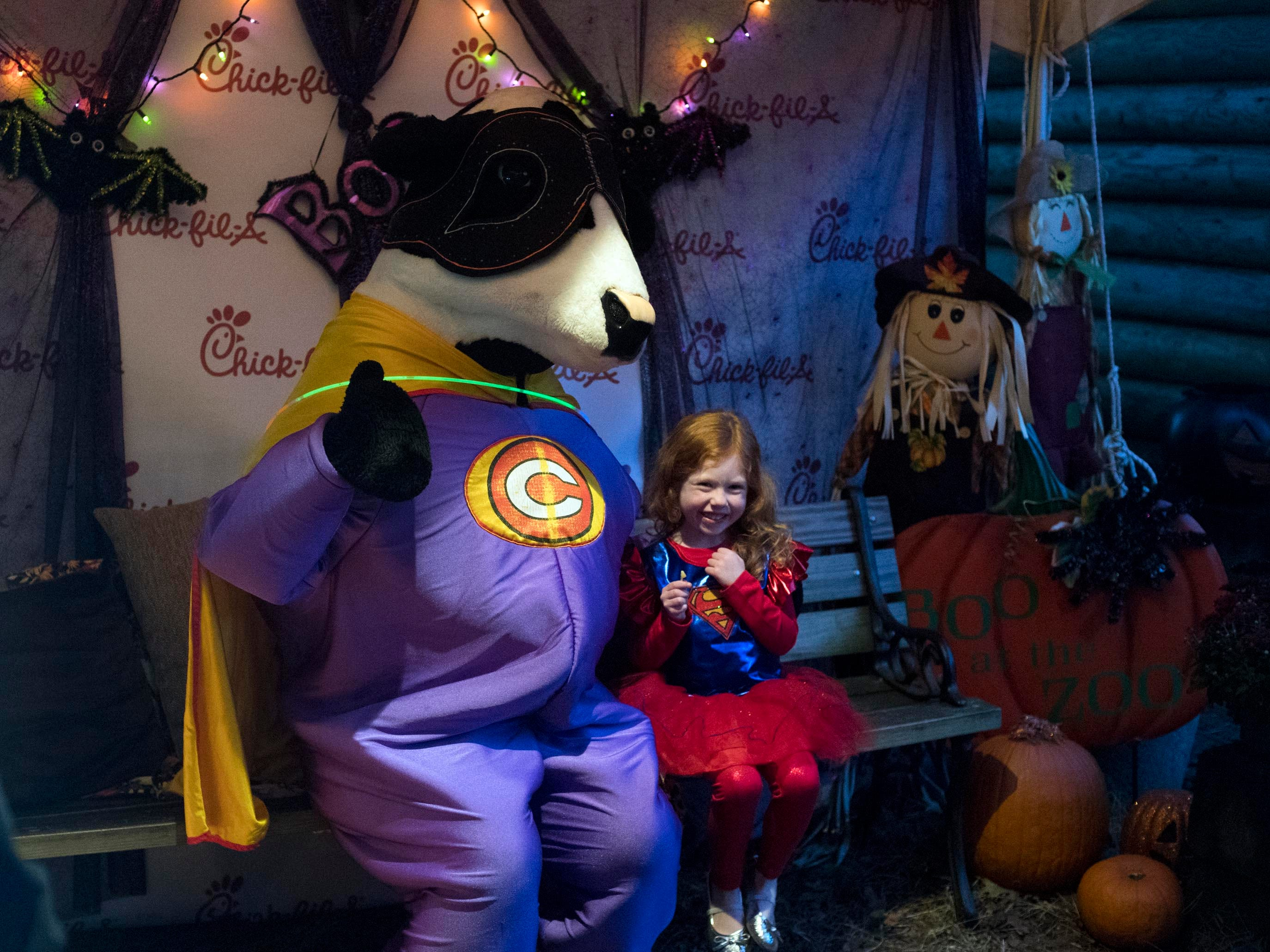 The Chick-fil-a mascot at super girl sit together for a photographer during Zoo Knoxville's Boo! at the Zoo presented on Saturday, October 20, 2018.