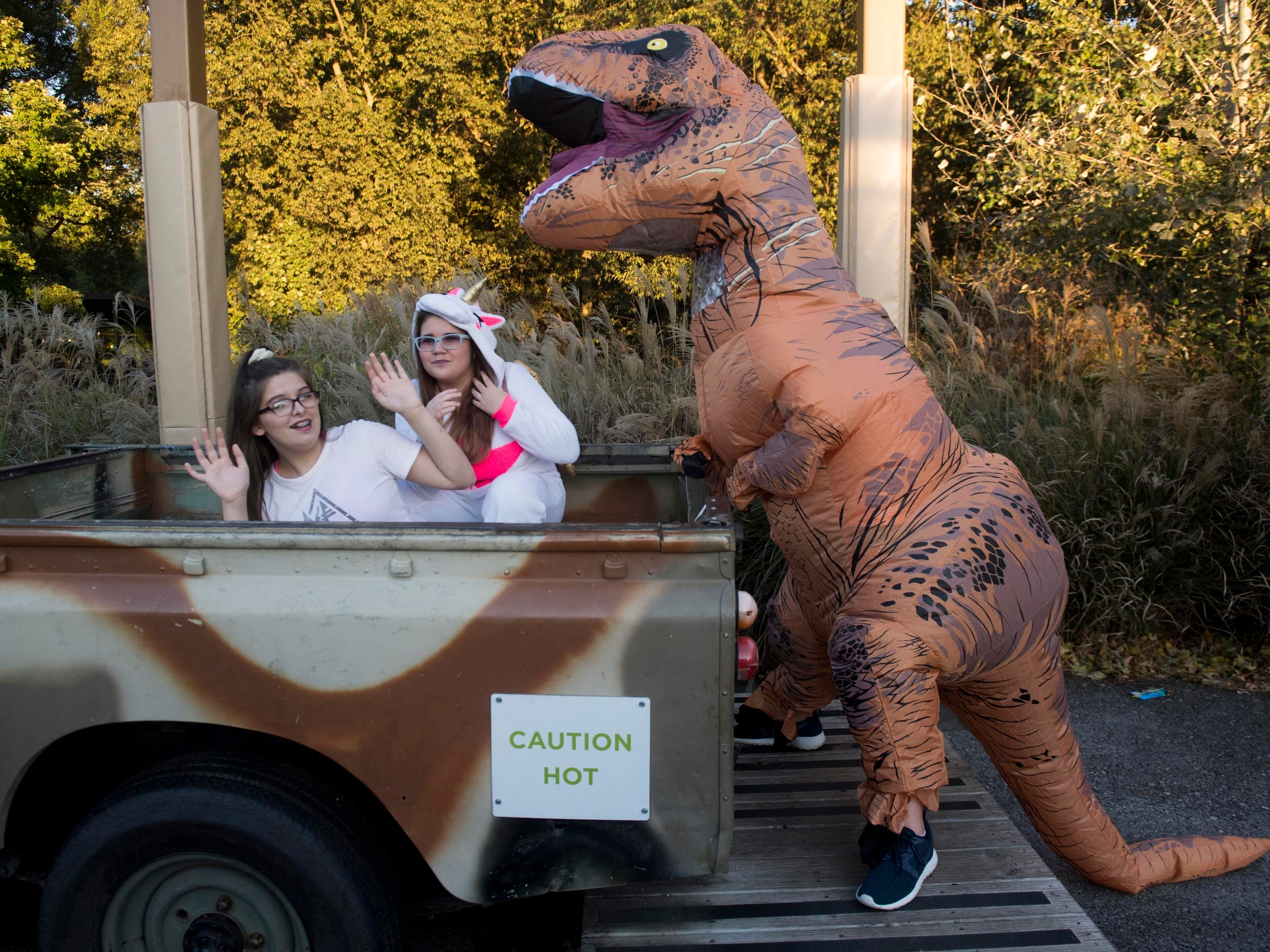 Jaclyn Gibson, left, and McKenzie Elliott are attacked by Gabi Bunch as they pose for photographs during Zoo Knoxville's Boo! at the Zoo on Saturday, October 20, 2018.