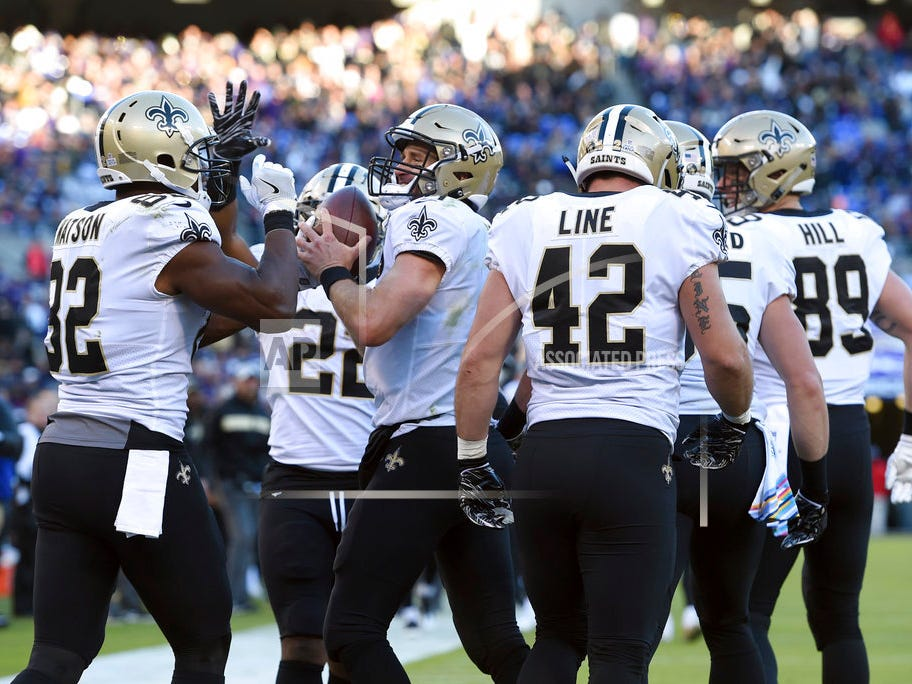 New Orleans Saints quarterback Drew Brees, center, celebrates with teammates after throwing his 500th career touchdown pass in the first half of an NFL football game, Sunday, Oct. 21, 2018, in Baltimore. (AP Photo/Gail Burton)