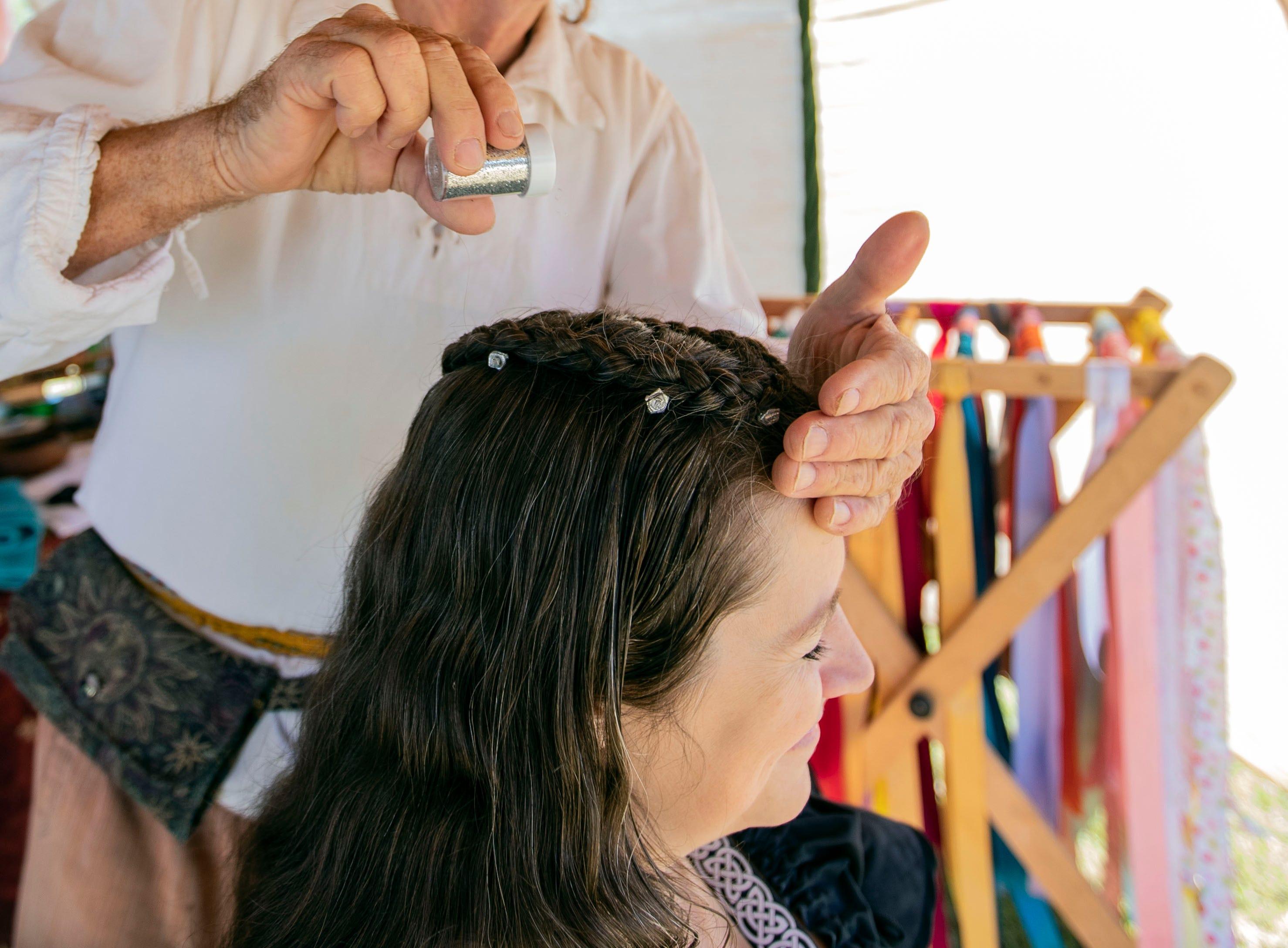 Renaissance Braids hairstylist Michael Grace styles Beth Kitchen hair at the Mid South Renaissance Faire Sunday October 21,2018