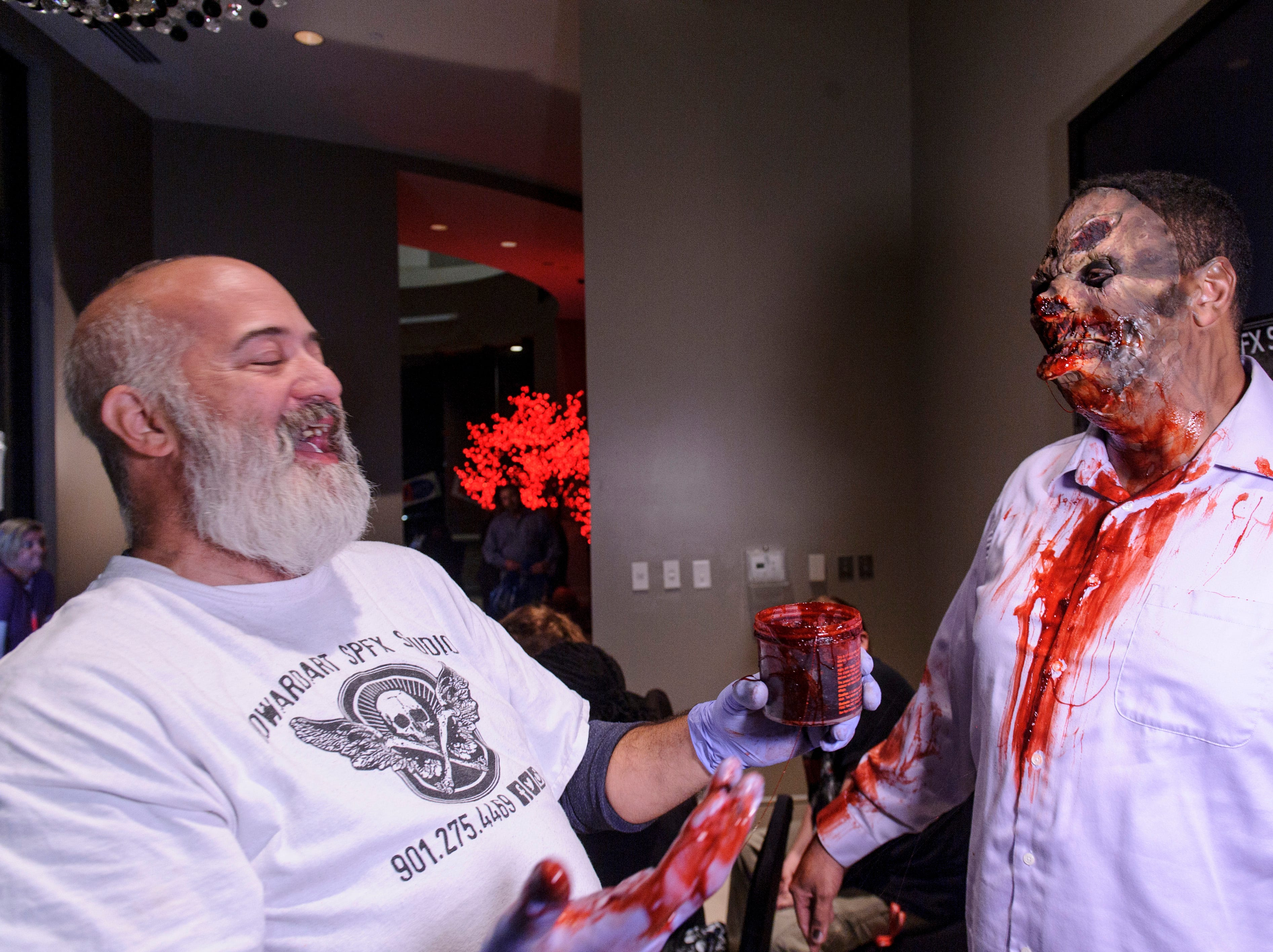 Artist A.G. Howard applies blood to Andrew Woods at the Zombie Prom on Saturday, Oct. 20, 2018.