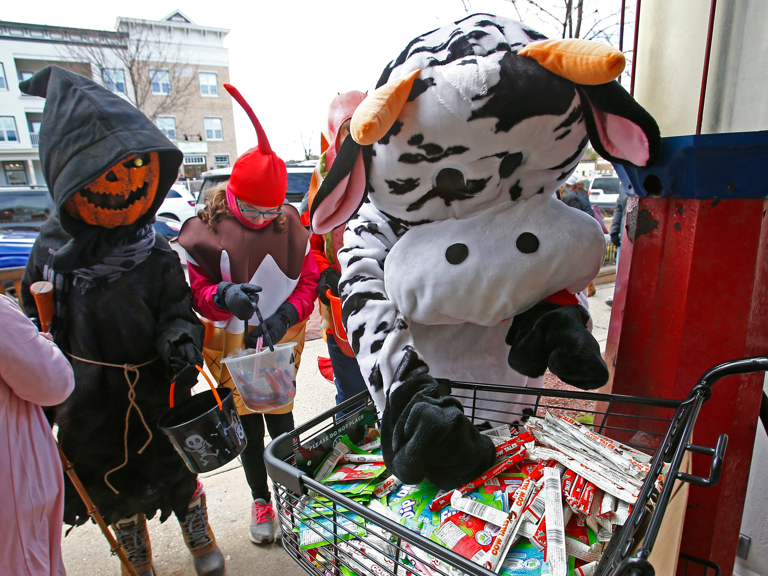Dressed as a cow, Kelly Newbauer hands out Cow Trail candies at the Day Break Mobile during the Delafield Business Trick or Treat on Oct. 20.