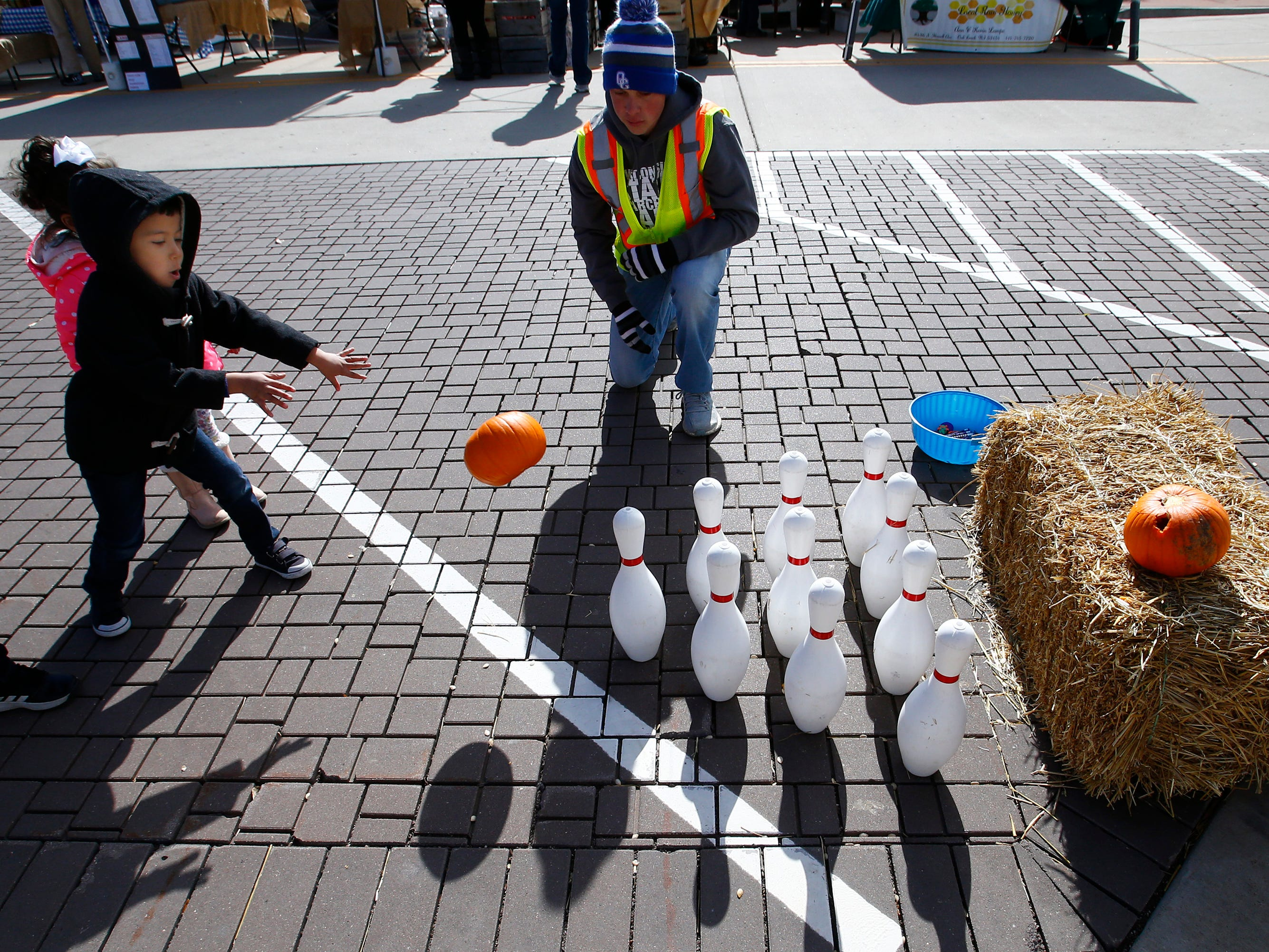 Adam Hasan of South Milwaukee tries Pumpkin Bowling during the Drexel Town Square Fall Festival on Oct. 20.