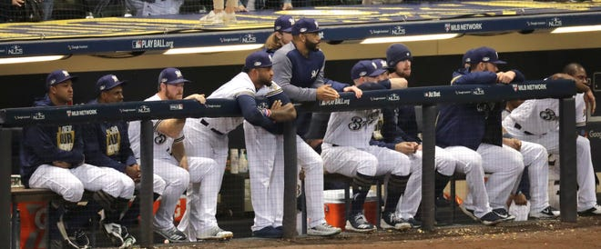 The Milwaukee Brewers dugout watches the Los Angeles Dodgers celebrate their National League Championship Series baseball win Saturday, October 20, 2018 at Miller Park in Milwaukee, Wis. The Los Angeles Dodgers beat the Milwaukee Brewers 5-1 to win the series.  MARK HOFFMAN/ MHOFFMAN@JOURNALSENTINEL.COM