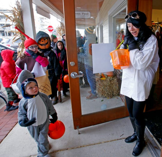 Dressed as a mad scientist, Jolene Van Den Elzen hands out candy from the the door of the Delafield Main Street Boutique during the Delafield Business Trick or Treat on Oct. 20, 2018.