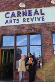 Becky Youngblood, left, and Salaam Green stand outside the Arts Revive sign where they met supporters at last Saturday's annual event.