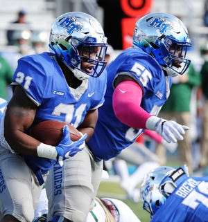 MTSU's Tavares Thomas (21) runs the ball as Carlos Johnson (55) block for him against Charlotte during the Homecoming game on Saturday, Oct. 20, 2018.