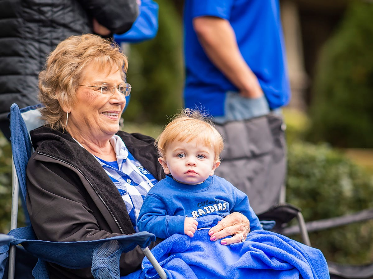 A grandmother holds her grandson while watching the parade.