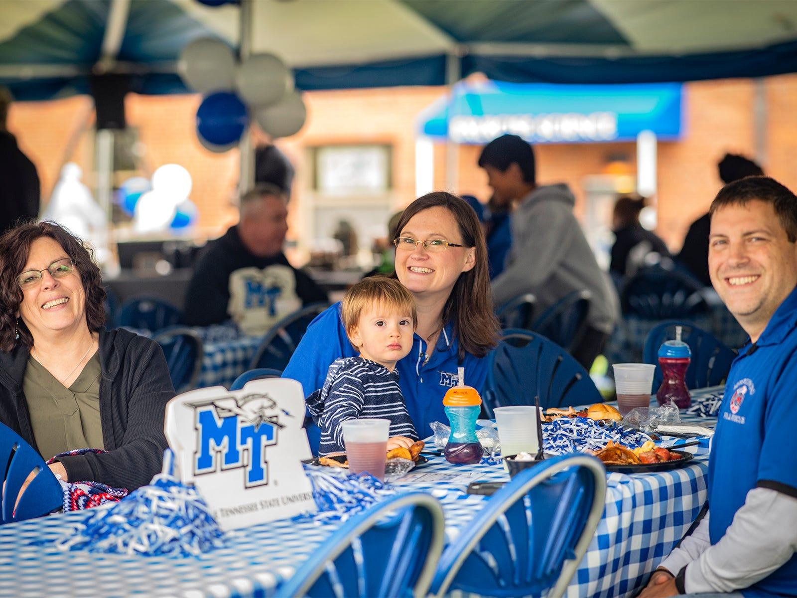 Jan Bartlett, Emily Munoz & son Logan, and Adam Munoz enjoy the Alumni tailgate luncheon after the parade.