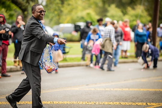 MTSU President Sidney McPhee passes out candy at the 2018 homecoming parade.