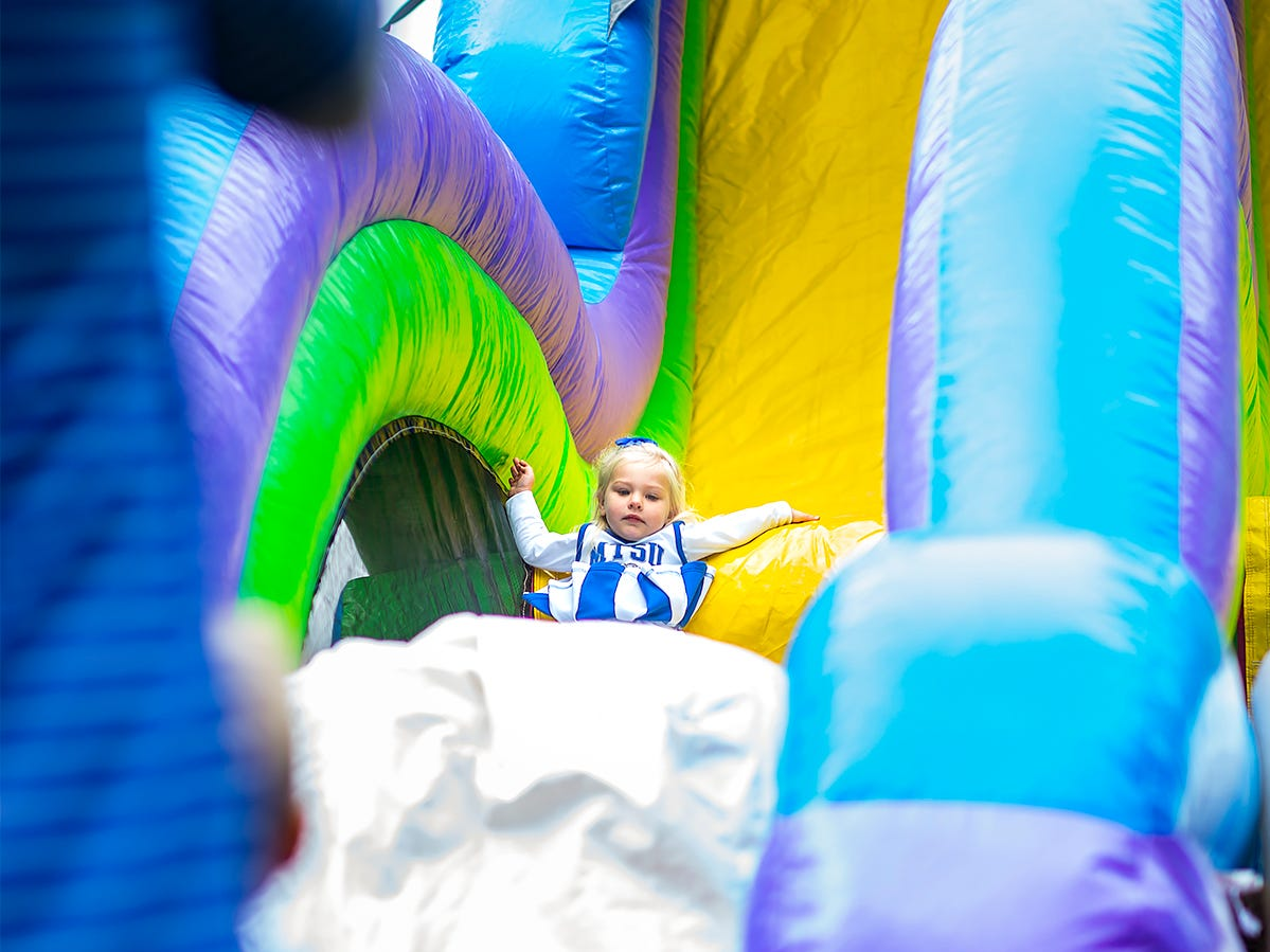 A baby Blue Raider goes down an inflatable slide during MTSU's homecoming festivities.