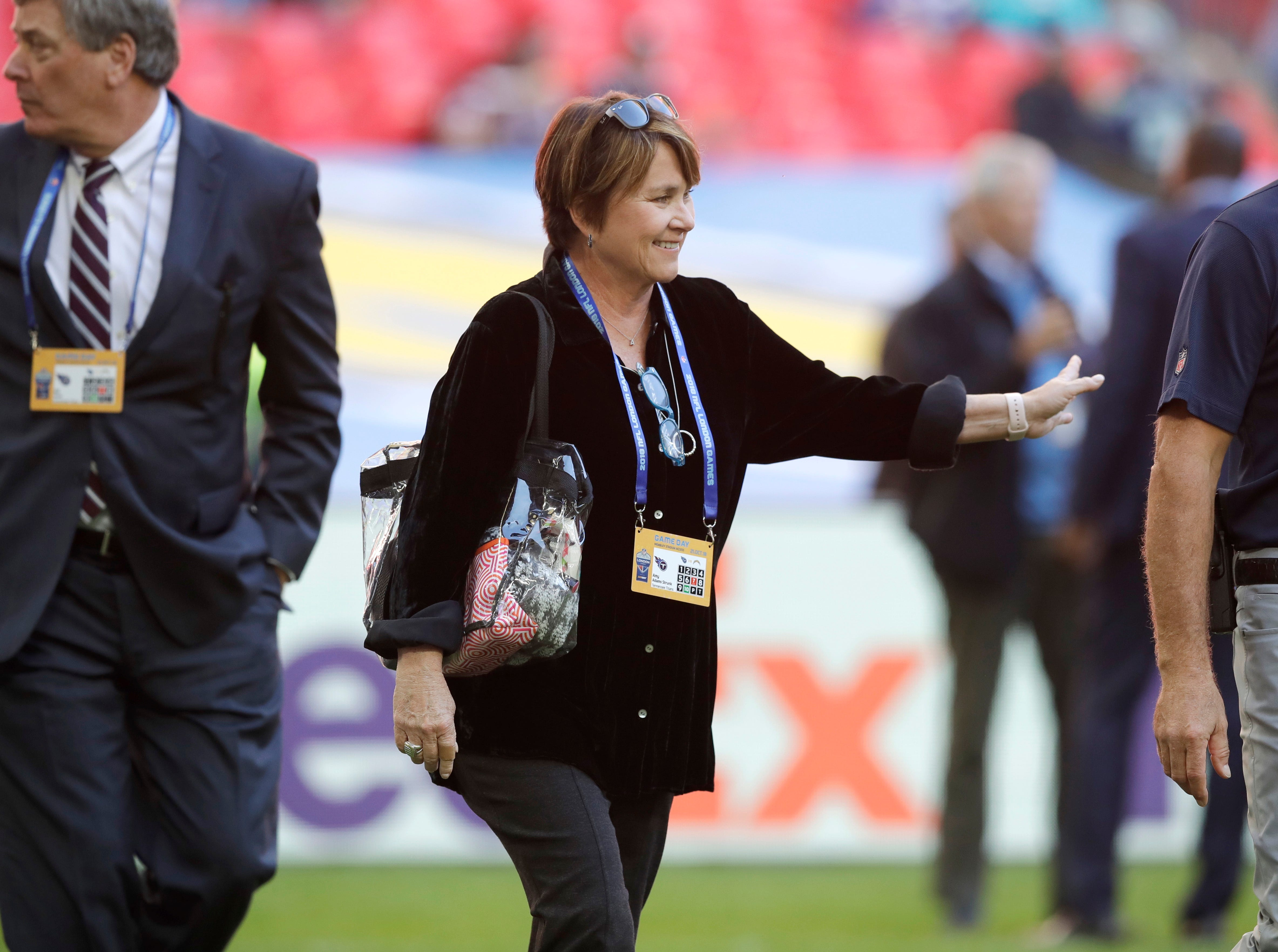 Amy Adams Strunk, center, the controlling owner of the Tennessee Titans smiles before an NFL football game against Los Angeles Chargers at Wembley stadium in London, Sunday, Oct. 21, 2018.