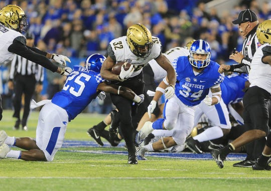 Oct 20, 2018; Lexington, KY, USA; Vanderbilt Commodores running back Jamauri Wakefield (32) runs the ball against Kentucky Wildcats safety Darius West (25) in the first half at Kroger Field.