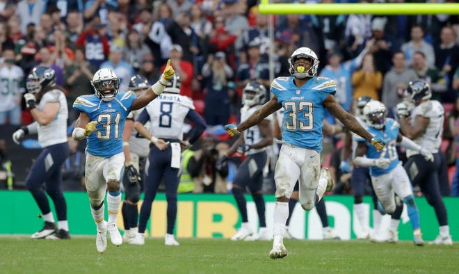 Chargers defensive back Adrian Phillips (31) and free safety Derwin James (33) celebrate after a successful defensive stop near the end of the second half Sunday.