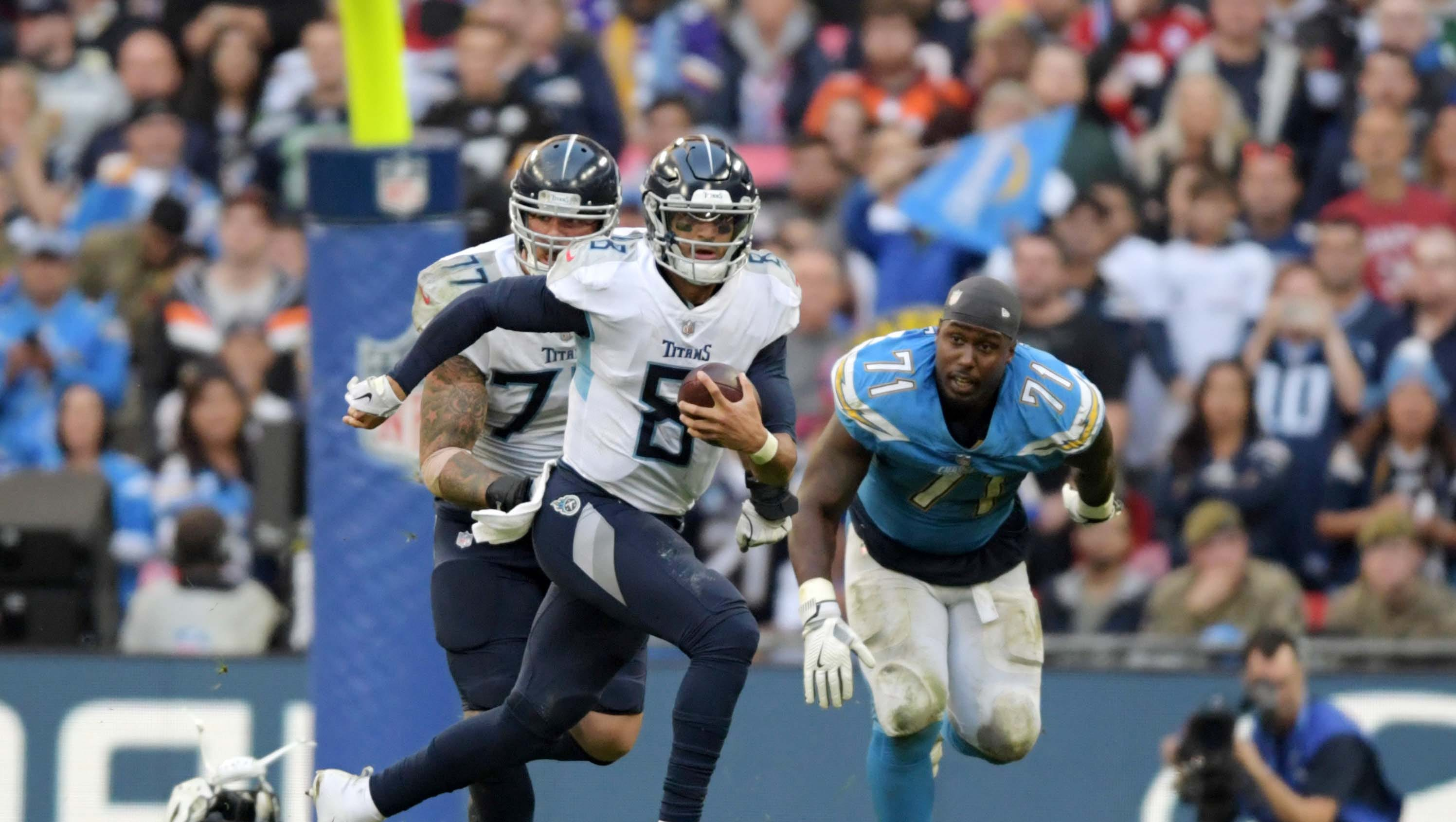 Oct 21, 2018; London, United Kingdom; Tennessee Titans quarterback Marcus Mariota (8) is pursued by Los Angeles Chargers defensive tackle Damion Square (71) on an 11-yard run in the fourth quarter during an NFL International Series game at Wembley Stadium. The Chargers defeated the Titans 20-19.